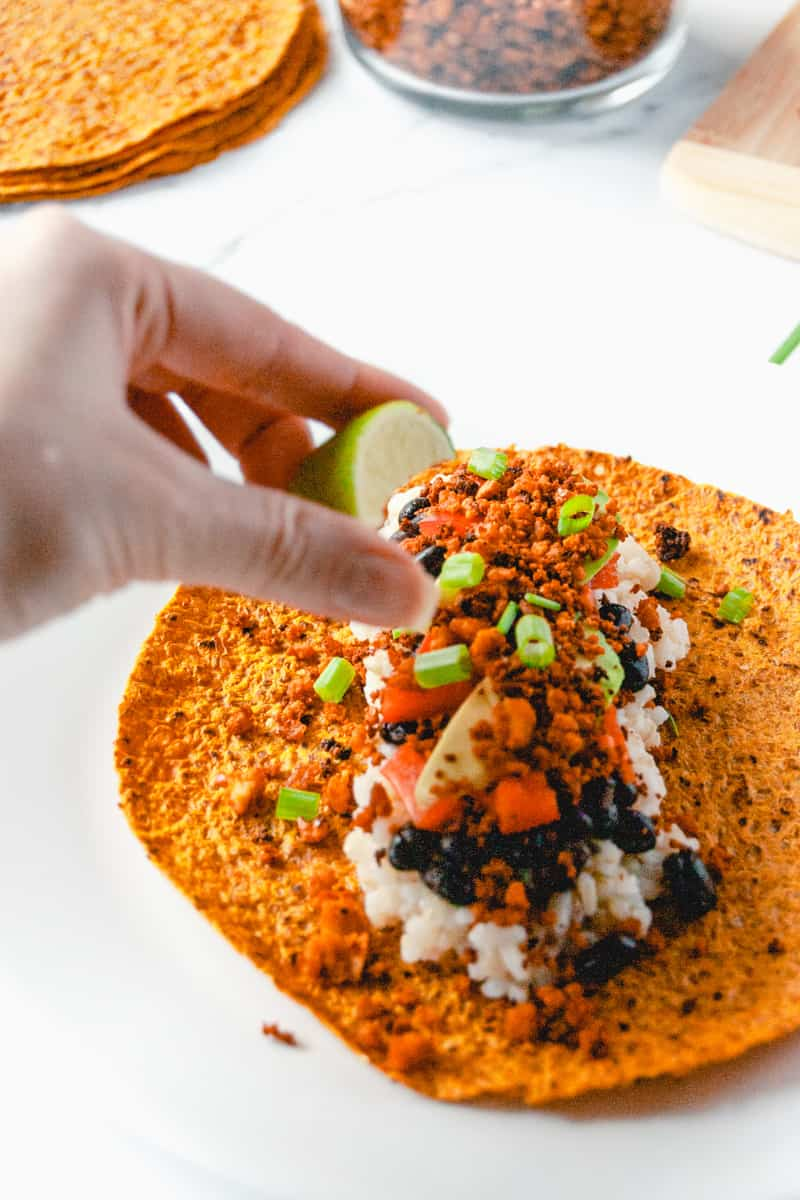 Woman squeezing a lime wedge onto a vegan taco topped with rice, beans, and vegan taco meat