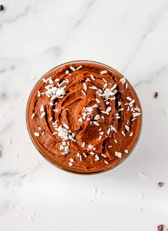 Bowl of Healthy Chocolate Mousse topped with shredded coconut on a marble countertop