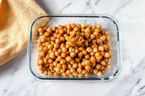 Cooked chickpeas in a shallow glass dish with a scoop of miso paste on top