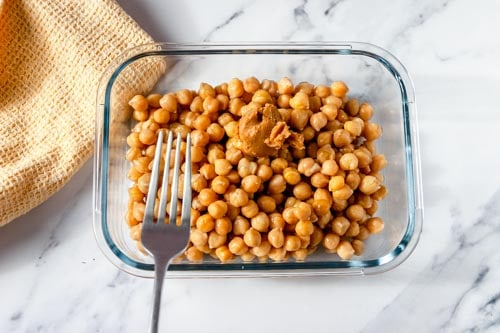 Glass dish full of chickpeas with a silver fork
