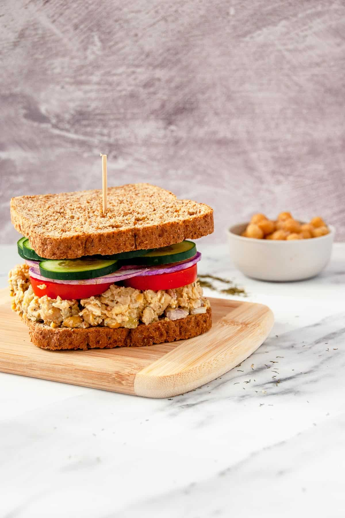 Vegan chickpea salad sandwich on whole grain bread with sliced vegetables piled on top