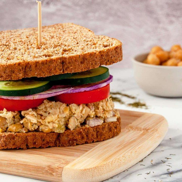 Chickpea salad sandwich on whole grain bread piled high with sliced veggies