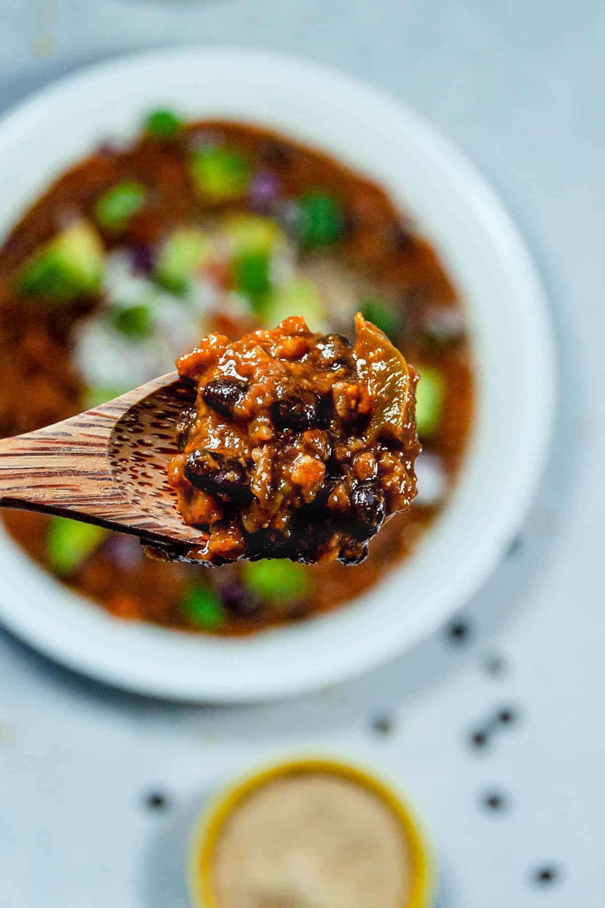 Close up of black bean and pinto bean chili on a wooden spoon