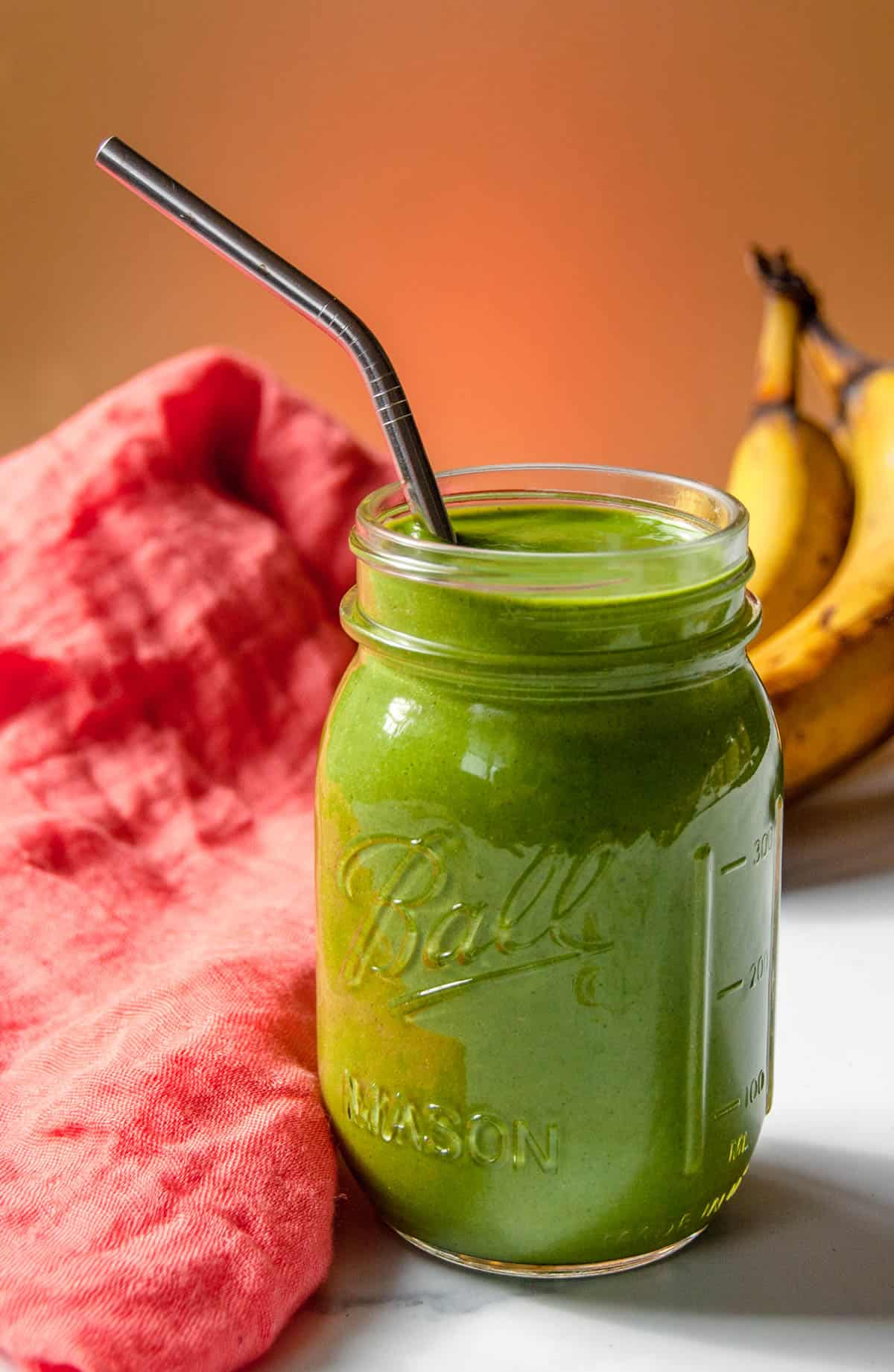 Whole food plant-based green smoothie in a mason jar with reusable straw