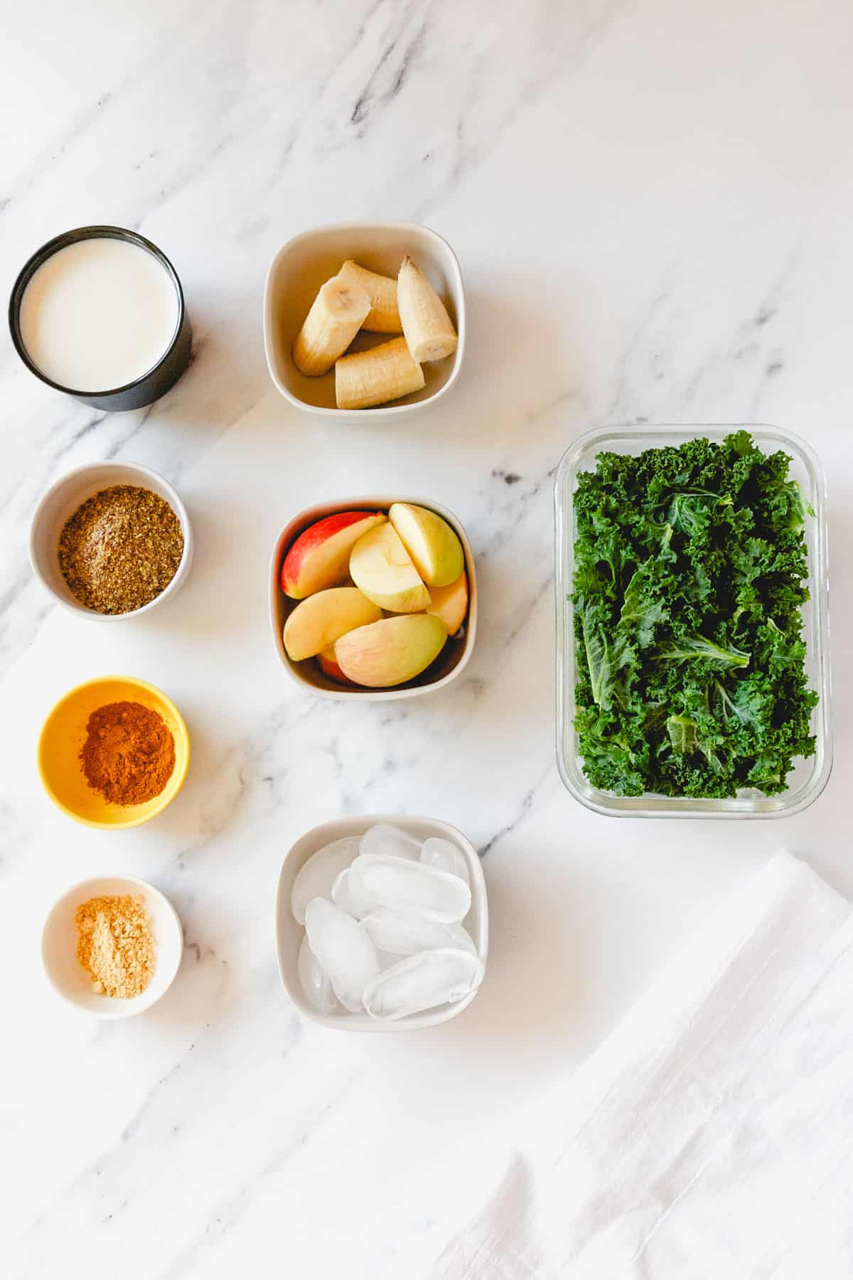 Apples, bananas, kale, flax, ginger, turmeric, ice, and non-dairy milk arranged on a marble countertop