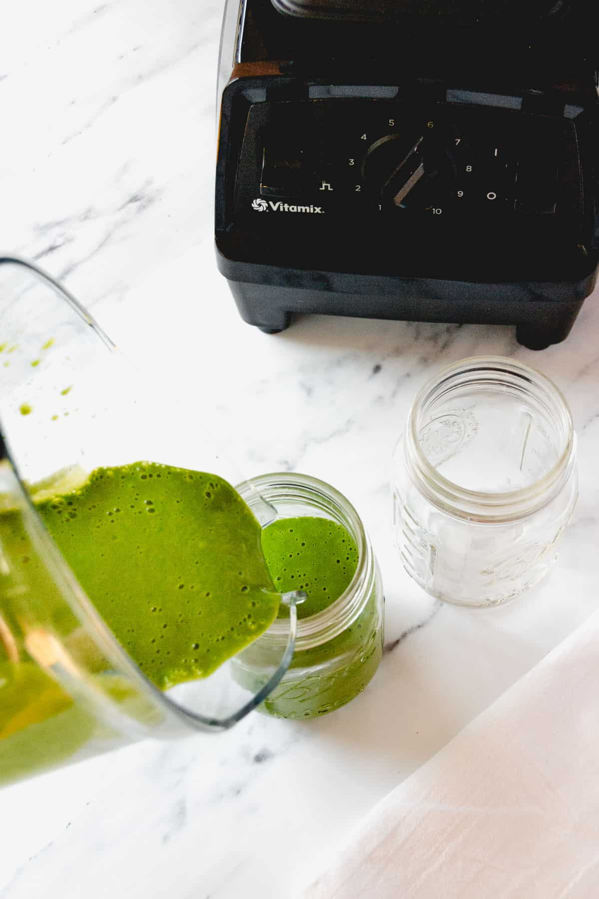 Pouring a bright green smoothie from a blender into a mason jar