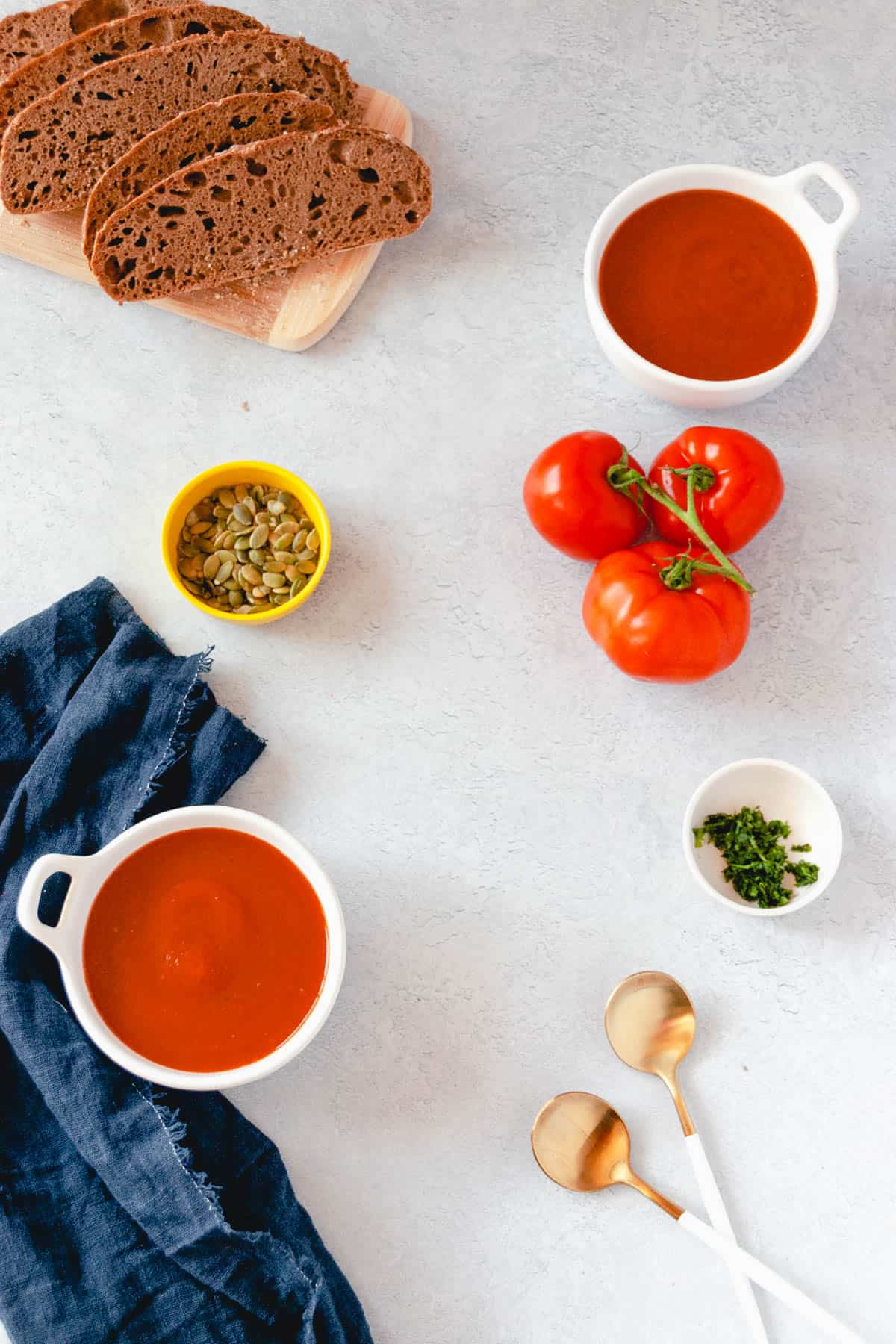 Two white bowls full of tomato soup arranged on a countertop with spoons, fresh bread, basil, and tomatoes on the side