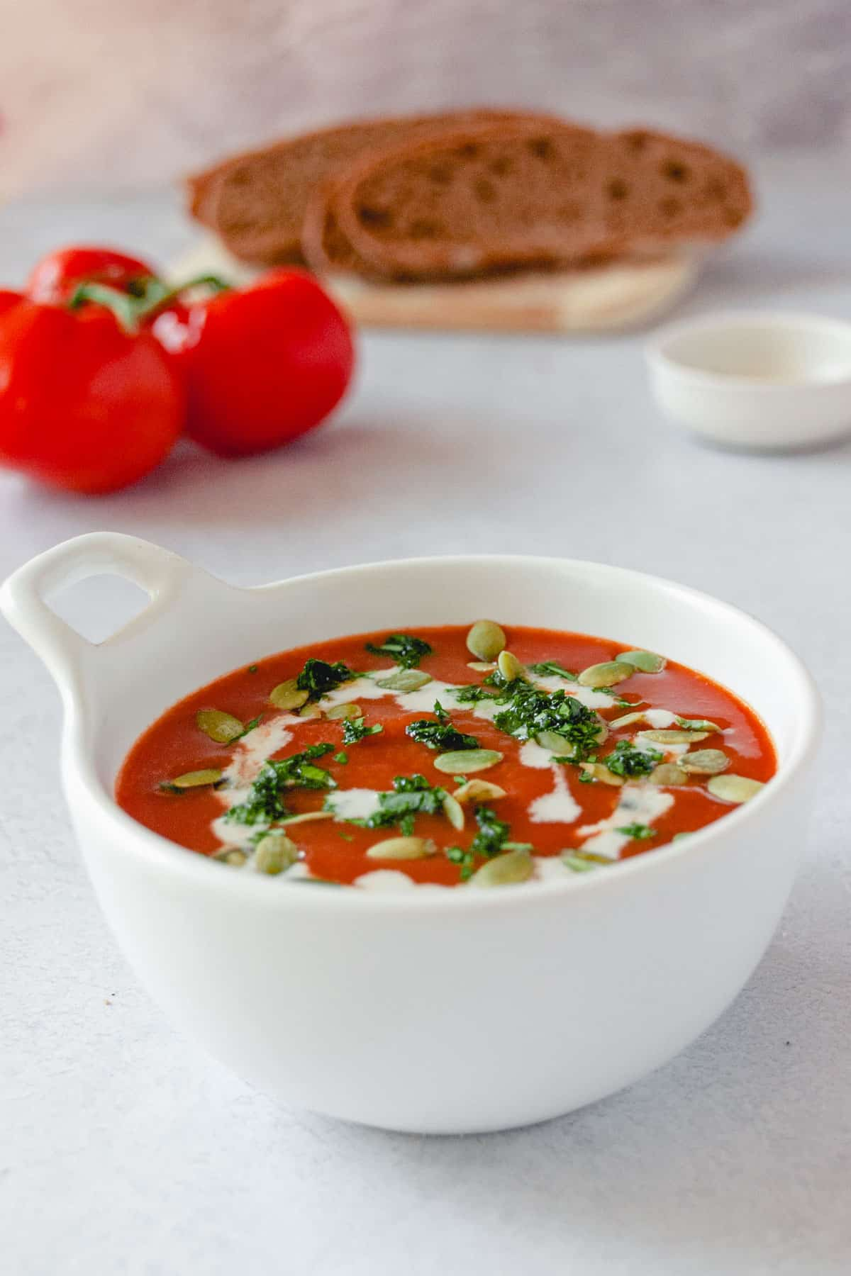 Close up of vegan tomato soup recipe in a white bowl topped with cashew cream, basil, and pumpkin seeds