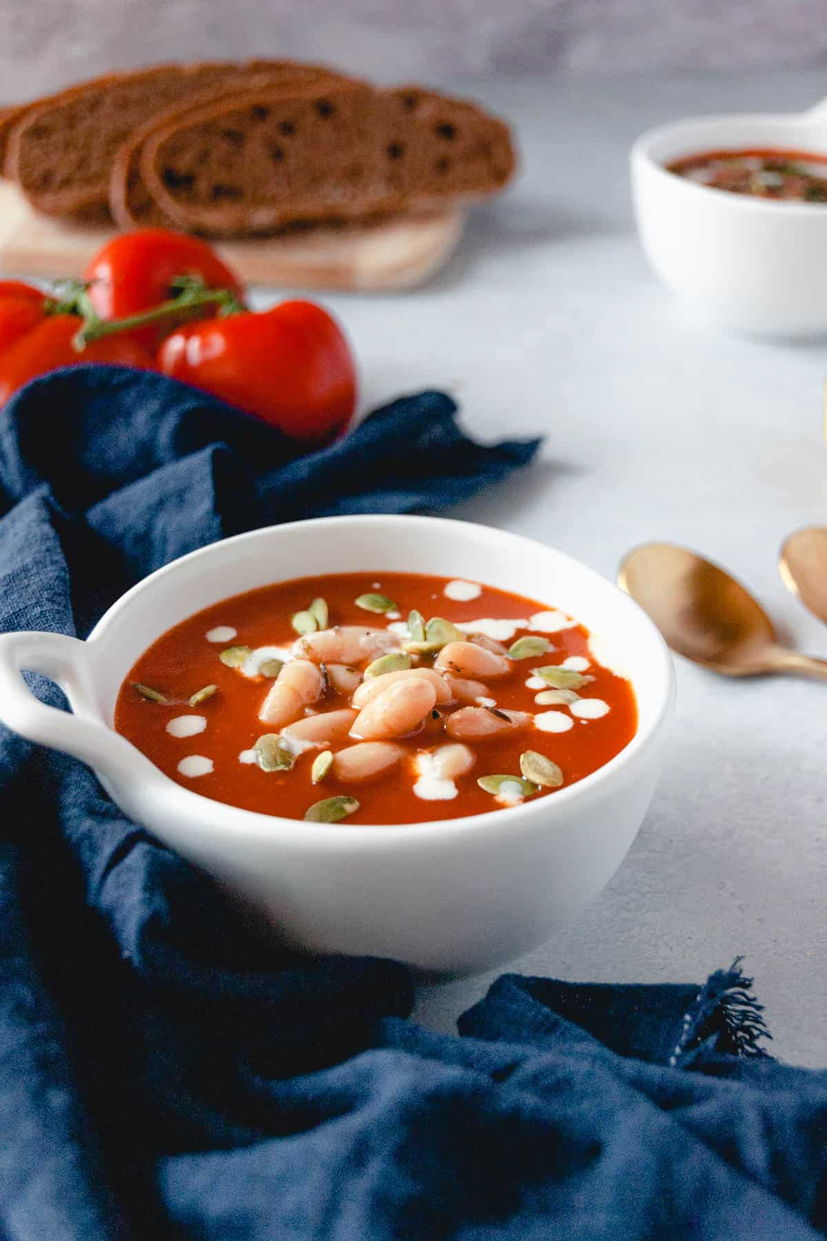 White bowl full of tomato soup with healthy toppings on top, navy blue linen on the side, and tomatoes and bread in the background