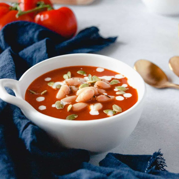 White bowl full of creamy vegan tomato soup with cashew cream on top and navy blue linen on the side
