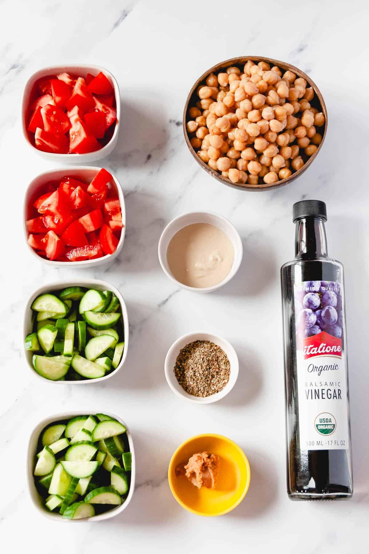 Tomatoes, cucumbers, chickpeas, tahini, balsamic, Italian seasoning, and miso arranged on countertop