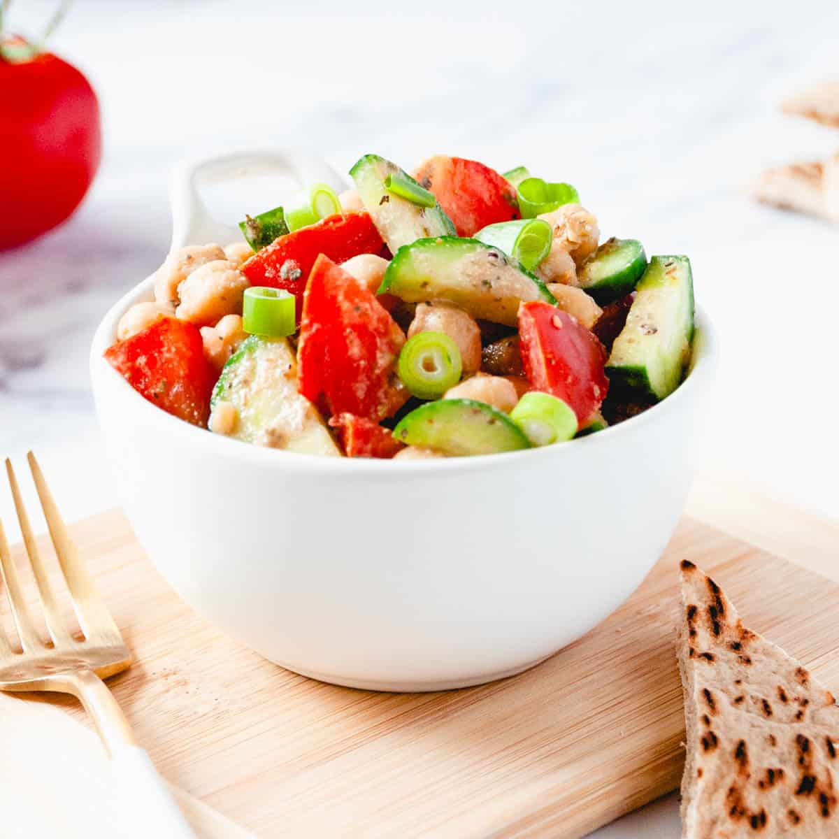 White bowl full of chickpeas, tomatoes, and cucumbers with homemade balsamic dressing