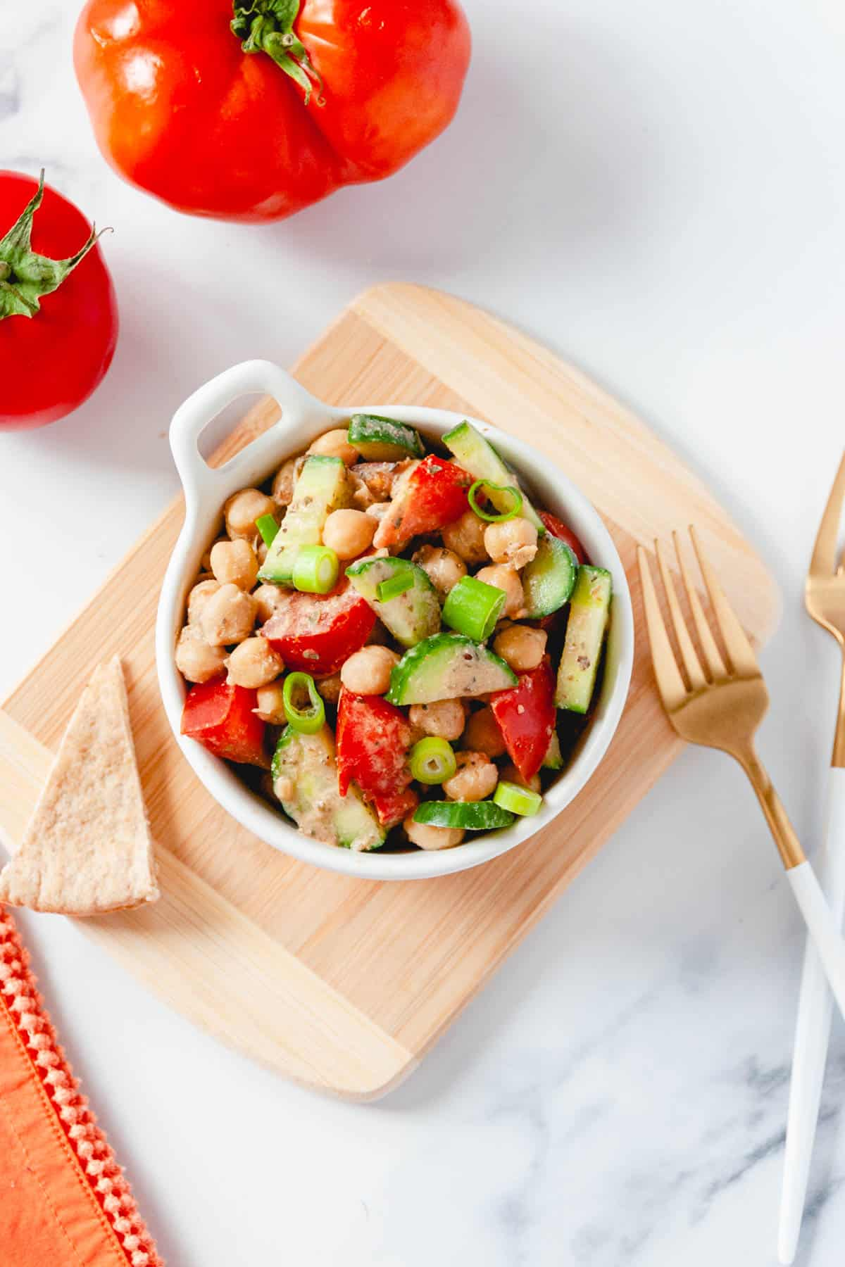 Bowl of balsamic chickpea salad, with pita bread, tomatoes, and forks on the side