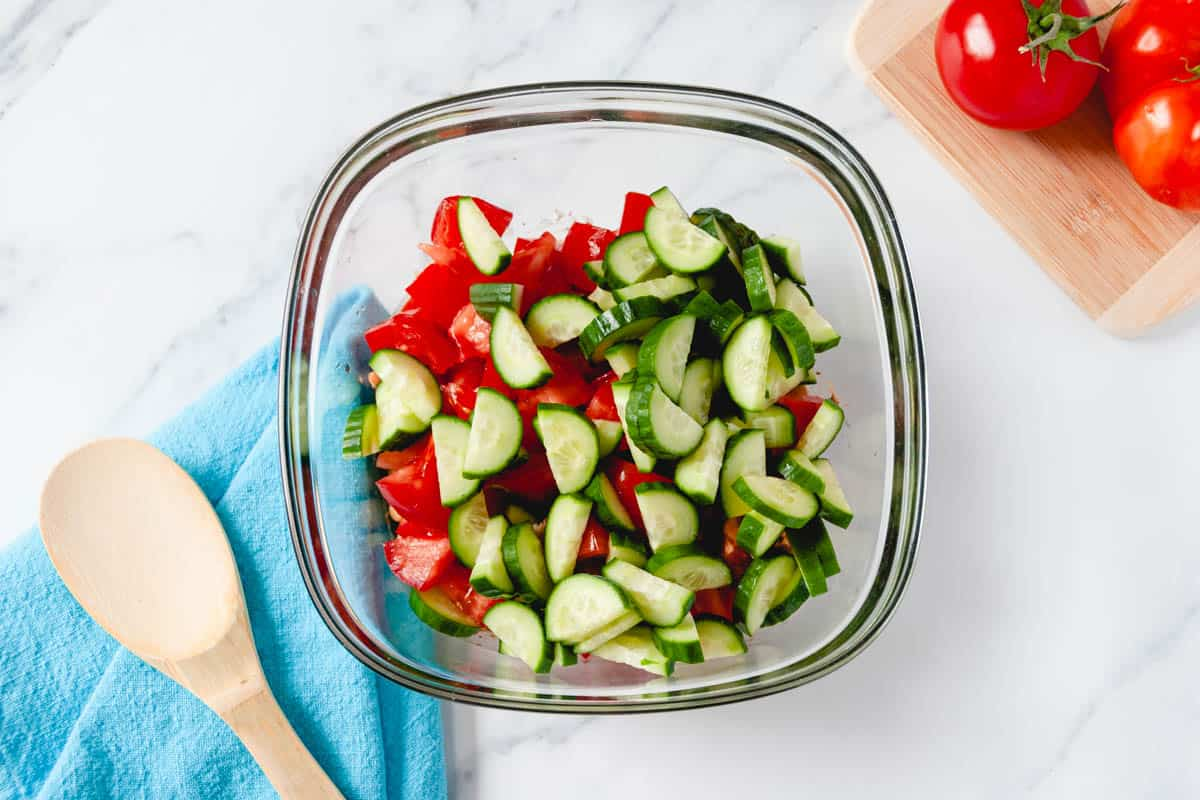 Large glass mixing bowl filled with dressing, chopped tomatoes, and sliced cucumbers