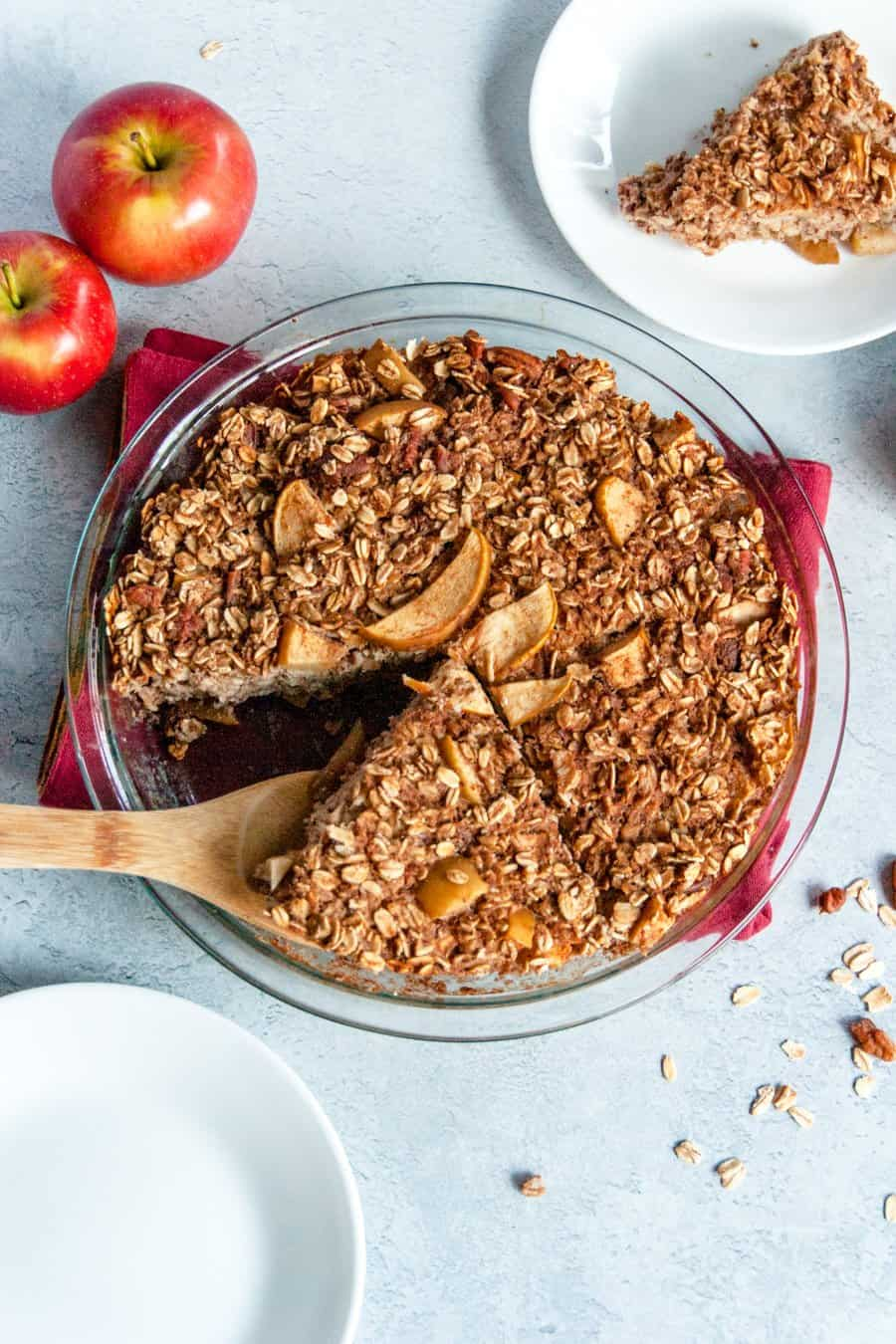 A round baking dish full of Apple Baked Oatmeal with a slice being served.