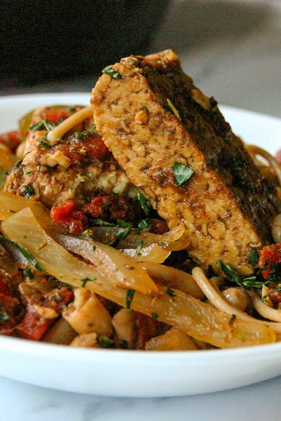 Close up of balsamic tempeh piled on top of pasta