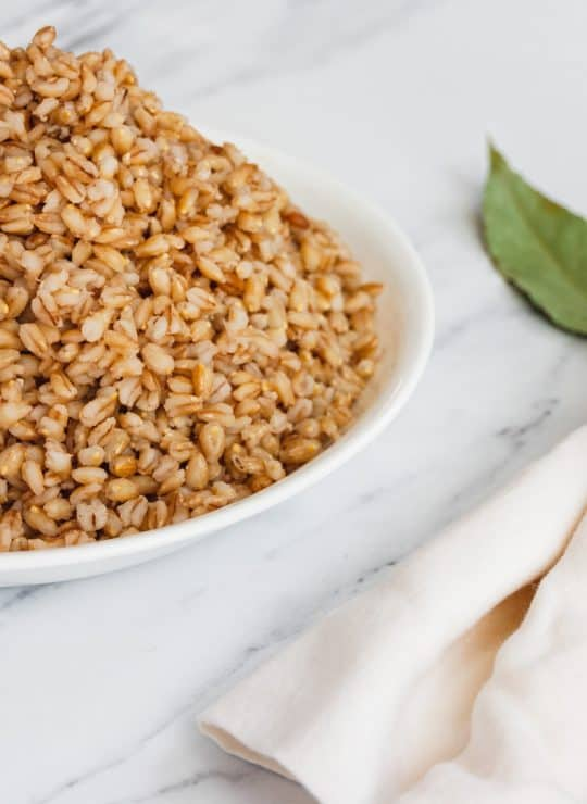 Full bowl of Instant Pot Barley with a wooden spoon and napkin