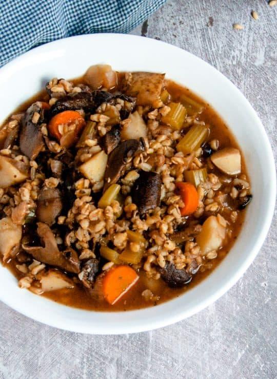 Vegan mushroom barley soup with spoon