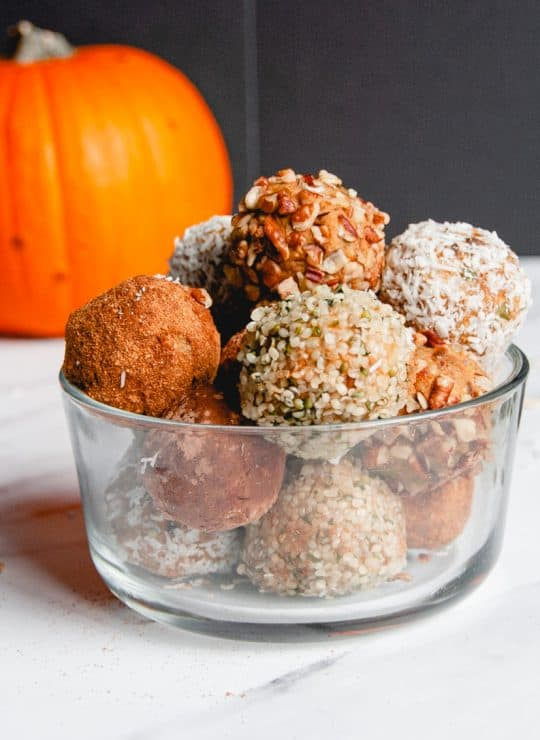 Bowl full of pumpkin energy balls covered in different healthy toppings
